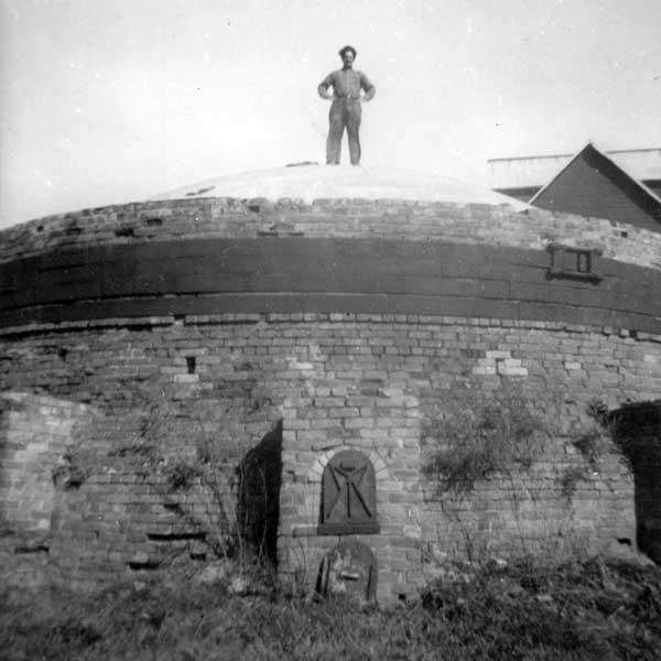 A worker monitors the 12- to 16-day process of firing freshly made bricks from atop the beehive kiln